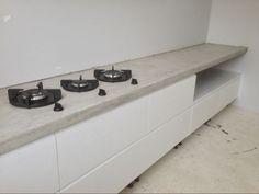 Mat wit geschilderde massief eiken keuken met gefreesde handgrepen en een betonnen blad met Pitt cooking. Ikea kasten