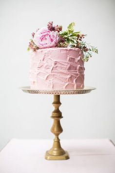Pink frosted cake on pedestal as centerpiece -- I love this idea instead of one big cake have these double as centerpieces.