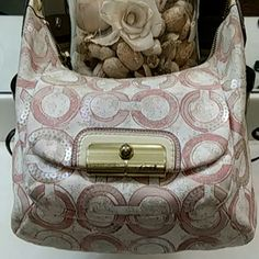 Authentic Coach purse Beautiful pale pink and cream colors with sequins.  All sequins are still in tact.  Normal wear but in great condition except for a little mark on the handle as shown in last picture.  It's a beautiful purse hate to part with it but its just  sitting in my closet.  Have always had lots of compliments as I'm sure who ever purchases will also. Coach Bags