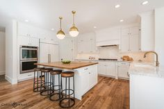 Stunning kitchen features a pair of Small Brass Hicks Pendants illuminating a white center island ...