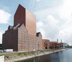 A house-shaped tower with no windows rises from the roof of an ageing warehouse to create a new archive building for the state of North Rhine Westphalia, Germany