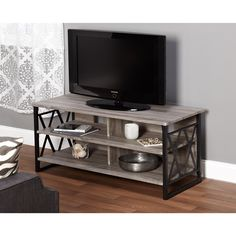 Organize your TV, consoles, and media collections with this stylish Simple Living three shelf stand. The durable MDF and PVC laminate construction and powder-coated X-design steel frame creates a dura