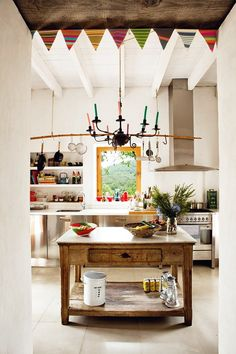 Bohemian inspired kitchen with a vintage wood island, and a brass chandelier