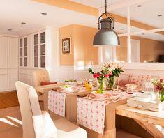 Comedor con mesa de madera, mantelería de flores y vista de armarios de almacenaje