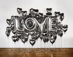 "We absolutely love this display!! We are definitely going to recreate this putting our own spin on it!  In this photo the word ""love"" is spelled using silver foil balloons surrounded by silver hearts. Imagine how this would look with your name, or spelling out ""Congrats"" surrounded by blue and yellow foil stars. The possibilities are limitless!"