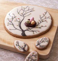 Sur un biscuit sablé, déposez un glaçage royal (sucre glace et blanc d'oeuf) et dessinez selon vos envies grâce aux feutres alimentaires ! Voici un arbre et son petit nid, qui trônera sur la table de Pâques ! Une idée piochée sur ce site anglais.