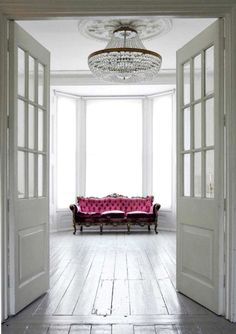 this chandalier and hot pink sofa are the beginnings of a great living room