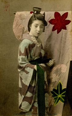 "A Geisha partially dressed, wearing only her Juban (inner kimono). Her hairstyle and the kimono hanging behind her are both in the Genroku style in imitation of the dress of the Genroku period (1688 -1703), a fashion that became popular amongst Tokyo Geisha around 1905. This postcard is captioned ""A Japanese Singer in the Dress of Olden Times"", Geisha were often referred to as ""Singing Girls"" by Western commentators during this period, while Maiko and Hangyoku were referred to as ""Dancing…"