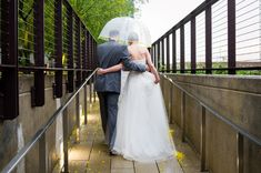 Bride and groom walking together hiding under a clear umbrella with yellow trim