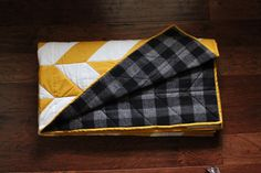 This throw quilt is perfect for the cozy months! Features a mustard and white herringbone pattern on the front with black and grey plaid flannel on the back. Great for picnics, hammocking, bonfires, or as a statement piece on your couch. This quilt is one that will last many years.  This quilt is handmade with high quality 100% cotton quilting fabrics and flannel material. Size: 50 x 65  FREE SHIPPING. Only in U.S.  --------------------------  Wash on cold. Hang dry…