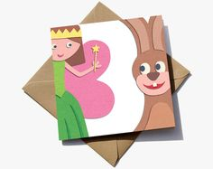 3rd birthday card for a girl. The number 3 is in the negative space between a fairy and a bunny rabbit.  The cute characters have the appearance of sugar paper giving them a playful quality that children will love.