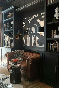 Black bookshelves and tan Chesterfield