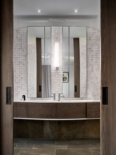 In this modern bathroom, a custom wood vanity is a strong contrast to the white marble tiles, while the mirrors make the space appear larger. #Bathroom #MarbleTiles #WoodVanity