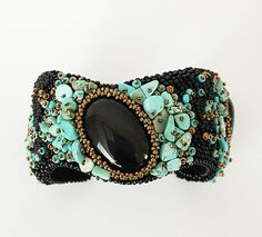 This bracelet is a mix of black, turquoise and gold colours. Focal is a large black onyx cabochon, surrounded with turquoise gemstone chips and black and gold miyuki seed beeds. The bracelet contains a metal brass cuff within the embroided fabrics for shape. The backing is black ultra