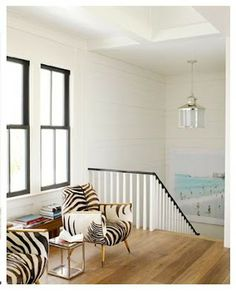 zebra chairs, black window frames and stair rail, white walls, beach photo