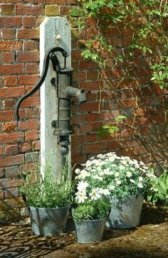 Flower Garden in old metal buckets and vintage water pump.. What a great idea!