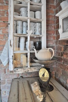 Cabinet, faced with an old window frame, holds a collection of ironstone cups - on an brick wall