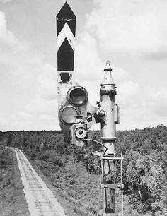 """Close-up of an upper-quadrant semaphore signal. Perhaps the most classic of all railroad signals, the semaphore, came into general use in the 1860's. This type, based on an ancient form of communication that used a moveable """"arm"""" or """"blade,"""" soon became by far the most common signal. Various signal indications were conveyed by setting the blade in different positions. The problem of night visibility was addressed by using lamps in conjunction with the blade. Semaphores were constructed with…"""