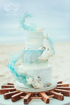 This cake is a work of art. Whimsical hand painted watercolor over fondant in soft blues and turquoises fully surrounded by a floating sugar sculpture made that mimics the salty sea, waves and shells. Amazing, right?