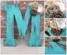 Large thin wooden letter M that has been stained and painted turquoise with a distressed technique. 3 flowers are placed made out of burlap,