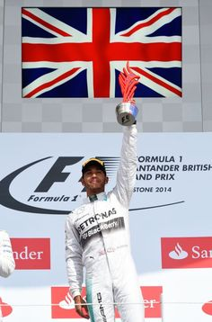 Lewis Hamilton of Great Britain and Mercedes GP celebrates on the podium after winning the British Formula One Grand Prix