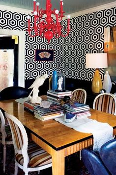The Van Devenders papered the dining room in a bold, black-and-white hexagonal print by Tres Tintas Barcelona. With such a graphic-patterned canvas to work with, Michel scaled back the layering of patterns by painting the existing chandelier a bright red and adding a modern dining table accented with antique chairs covered in a traditional stripe-patterned fabric. wall paper for mudroom