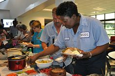 Geneva Moore, front right, and Mike Pensock go through the serving line at the Staff Luncheon.