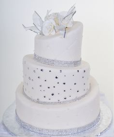 Pastry Palace Las Vegas - Wedding Cake #555 – A Gem of a Wedding. Three tier topsy-turvy layers in snow-white fondant, accented with sparkling silver gems and bands of crystals.