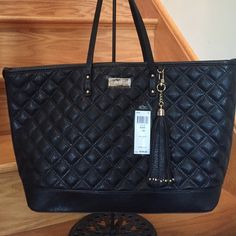 BCBG Black Quilted Bag, brand new This lovely bag was purchased for me, but I already had a couple of black bags like this. I held onto it for awhile, but would rather see someone using it. It's gorgeous. It's quilted, has gold feet on the base, is 15 inches across the base and 20 across the top. There is 8.5 inches from top of purse to top of strap, so it's perfect to drape across your elbow. Interior pockets, one zips. Clasp closure. Priced to sell. BCBG Bags