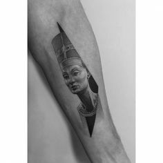 Nefertiti tattoo on the inner forearm.