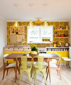 """The 12sqm kitchen sports a """"mustard and custard"""" colour scheme with Orla Kiely Giant Rhododendron wallpaper and ..."""