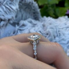 This unique princess cut diamond halo engagement ring, features a prong set princess cut center diamond, set on point and encircled with shared prong set diamonds. The detailed shank is artfully embellish with diamonds for an added touch of glam.