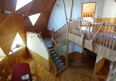 Upper level geodesic dome house,  oak floor, wood wall, table, red tablecloth, chairs, triangle windows, skylights, wood columns, natural wood rails, wood stairs, wood ceiling, wall light fixtures, home for sale, 9121 CR 23 Brainerd MN 56401 Red Tablecloth, Geodesic Dome Homes, Wood Columns, Wall Light Fixtures, Dome House, Wood Stairs, Safe Haven, Skylights, Wood Ceilings