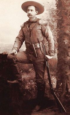 KANSAS SCOUT WITH BOWIE KNIFE, HOLSTERED PISTOL AND WINCHESTER 1880s. Great cabinet card studio image of a Kansas scout with all the accoutrements: fringed jacket, Bowie knife, cartridge belt, holstered pistol, Winchester and knee-high boots. The photographer of this great image is C. E. Koentz, Onaga, Kansas