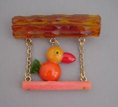 Adorable Shultz Bakelite bird swinging on a branch brooch.