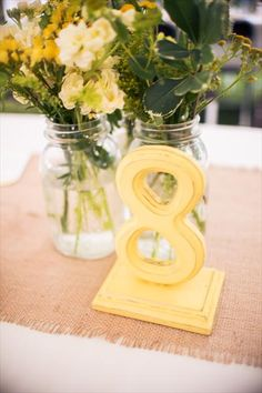 Table numbers painted yellow and made to look distressed. Mason jars with flowers to add to the other centerpieces.