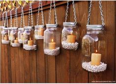 Mason Jars hanging from chains with candles in each and white bean filler