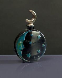 * SARI - «Lune de Miel» - (années 1920) Flacon en verre opaque noir pressé moulé rehaussé d'émail vert bronze, de section rectangulaire, panse en forme de disque, une face à décor moulé d'un croissant de lune au visage expressif et d'une pluie d'étoiles, bouchon laqué argent figurant un croissant de lune. modèle édité par la Verrerie Dépinoix