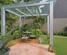 A modern grey gazebo wih wide plate glass roof completed with chairs and small…