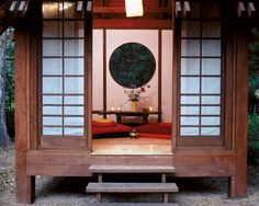 A Serene Asian-Inspired Garden—Japanese shoji screens traditionally are made from translucent rice paper, but the owners chose a durable, light-penetrating fabric that will prevail in harsh weather. It allows filtered light without sacrificing privacy. The floor is salvaged pine planks from a park ranger's mountain cabin, and a round window brings in the garden even when the doors are closed.