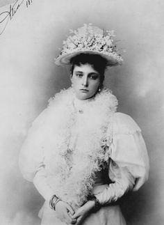 """Alexandra Feodorovna, a imperatriz da Rússia. Ela está em pé de frente para a câmera e tem as mãos entrelaçadas. Ela está usando um boá de penas, um chapéu decorado com flores e uma série de pulseiras. A fotografia é assinada e datada """"Alix 1895"""", no canto superior esquerdo."""