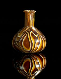 A band agate glass. Italy or Eastern Mediterranean, 1st century B.C. - 1st century A.D. Small bottle with piriform body and short cylindrical neck. Decorated with white and brown and dark brown bands. Intact. Very rare glass type!