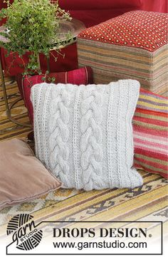 Knitted pillow with cables and false Fisherman's Rib. The piece is worked in 2 strands DROPS Air.