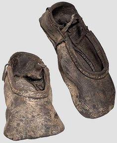Ein paar Kuhmaulschuhe,  deutsch um 1530. Gut erhaltene Schuhe aus braunem Leder mit breiter Spitze. Verstärkte Oberkante und Ferse, seitlich Reste der ledernen Schuhbänder. Auf der Sohle des einen Schuhs aufgeklebter Zettel mit Beschreibung der Herkunft aus dem Zwischenboden eines Hauses in St. Gertraud in Südtirol. Länge je ca. 23,5 cm. Extrem seltener, früher Schuhtyp, der sich nur in wenigen einzelnen Exemplaren erhalten hat. Kostümkundlich von großer Bedeutung.