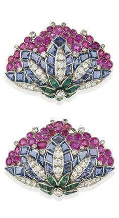 A PAIR OF VINTAGE MULTI-GEM AND DIAMOND CLIP BROOCHES, CIRCA 1950. Each designed as a stylised flowerhead in profile, with brilliant-cut diamond centre to the calibré-cut emerald calix and diamond and square-cut sapphire petals, with vari-sized oval-cut ruby cluster surmount, 5.0cm, with French assay marks for platinum and gold. #vintage #brooch