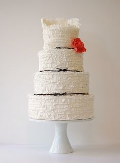 White ruffle wedding cake with black bows and red flower by Maggie Austin Cakes