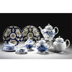 A group of Worcester blue and white `Three flower' pattern printed wares circa 1770 comprising: a teapot and, cover, sugar bowl and a cover, milk jug, slop bowl, six teabowls and six saucers, teapot and a matched cover; also a teapot and cover, circa 1775, printed with `The Mother and Child and Man Fishing' pattern; three other Worcester blue and white teapots and covers; a composite Worcester and Caughley butter dish, cover and stand; and a pair of Worcester scale-blue ground fluted plates…