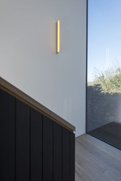 Image 10 of 22 from gallery of House 19 / Jestico + Whiles. Photograph by Grant Smith Stairs Window, Pendant Light Fitting, White Fireplace, Dormer Windows, Walnut Dining Table, Timber Flooring, House Roof, Cladding, Architecture Design