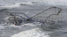 Waves wash over a roller coaster from a Seaside Heights, N.J. amusement park…