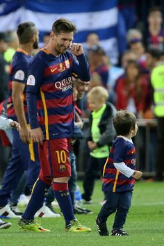 """Barcelona's Argentinian forward Lionel Messi looks at his son after winning the Spanish """"Copa del Rey"""" (King's Cup) final match FC…"""